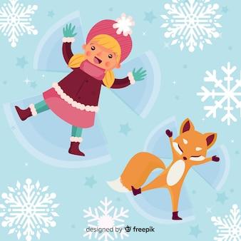 Mädchen und fuchs, die schneeengel machen