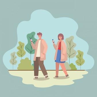 Mädchen und junge mit smartphones am park