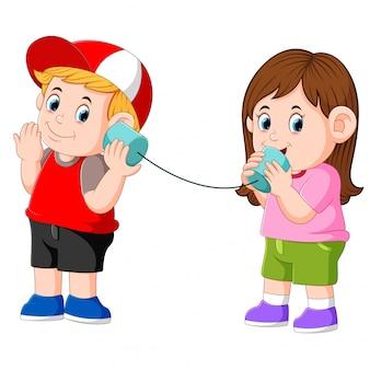Mädchen und jungen, die experimentieren, sprechend auf einem verdrahteten blechdosentelefon