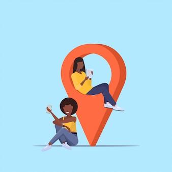 Mädchenpaar unter verwendung von geo-tag-zeiger-afroamerikanerfrauen, die digitale geräte nahe standortmarkierungs-gps-navigationskonzept in voller länge halten