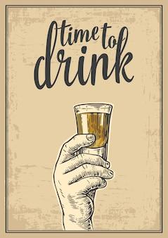 Männliche hand, die einen schuss alkoholgetränk hält. weinlesegravurillustration für etikett, plakat, einladung zu einer partei. zeit zu trinken. beiger hintergrund des alten papiers.