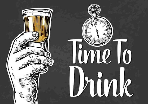 Männliche hand, die einen schuss alkoholgetränkegravur hält einladung zu einer partyzeit zum trinken