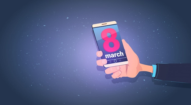 Männliche hand, die intelligentes telefon mit dem 8. märz-mitteilungs-glücklichen internationalen frauen-tagesfeiertags-konzept hält