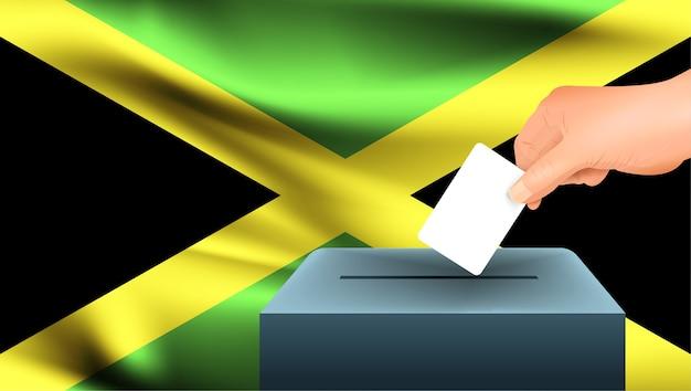 Männliche hand legt ein weißes blatt papier mit einer markierung als symbol eines stimmzettels vor dem hintergrund der jamaika-flagge nieder. jamaika das symbol der wahlen