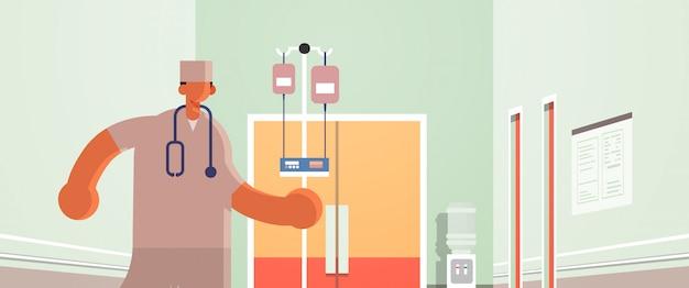 Männlicher arzt anästhesist hält tropfer medizin gesundheitswesen konzept krankenhaus medizinische klinik korridor innenraum in voller länge horizontale porträt flach