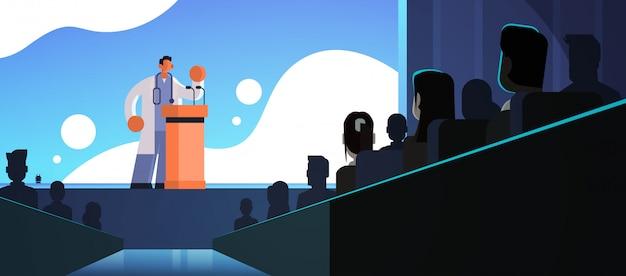 Männlicher arzt im weißen kittel, der rede von tribüne mit mikrofonen medizingesundheitskonzept menschengruppe silhouetten konferenztreffen seminar flach horizontal hält