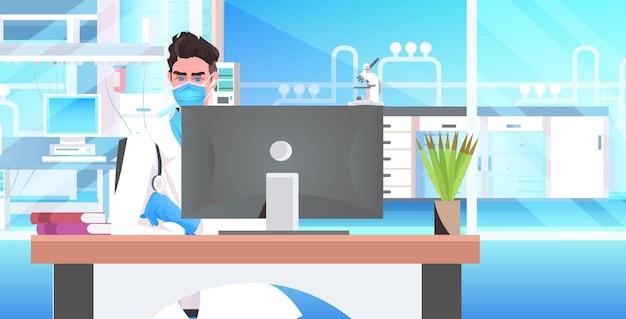 Männlicher arzt sitzt am arbeitsplatz facharzt in maske mit computermonitor online