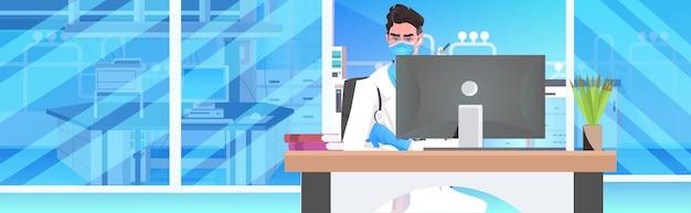 Männlicher arzt sitzt am arbeitsplatz medizinischer spezialist in maske unter verwendung der online-kommunikation des computermonitors