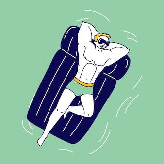 Männlicher athlet mit schönem bodybuilder-körper, der auf aufblasbarer matratze schwimmt
