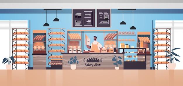 Männlicher bäcker, der tasche mit baguettes mann in der uniform hält, die frische backwaren in der horizontalen vektorillustration des backwarenporträts verkauft
