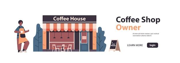 Männlicher barista im einheitlichen kaffeehausbesitzer im vorfeld, das nahe kaffeehaus steht, isolierte horizontale vektorillustration des kopienraums in voller länge