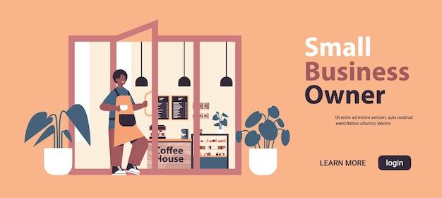 Männlicher barista in der uniform, die im modernen kaffeehauskellner in der schürze arbeitet, die tür-kleinunternehmerkonzept horizontale in voller länge kopierende raumvektorillustration hält