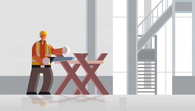 Männlicher baumeister schreiner mit handsäge sägen protokoll auf sägebock in holz beschäftigt arbeiter in einheitlichen baukonzept baustelle innen flach in voller länge horizontal
