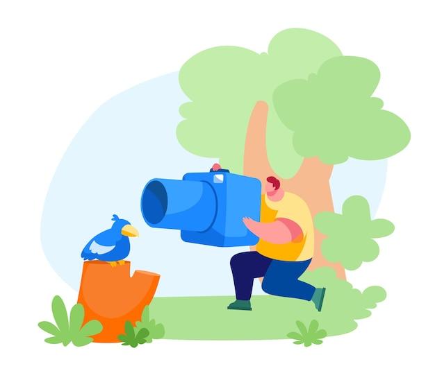 Männlicher charakter des jungen fotografen, der bild des niedlichen vogels macht