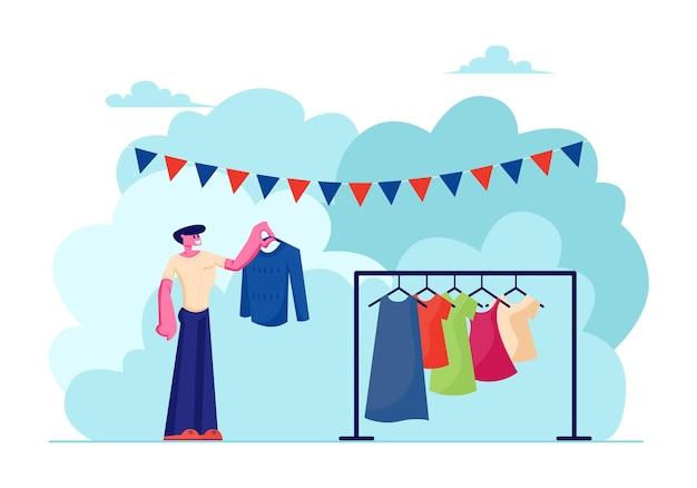Männlicher charakter wählen sie kleidung zum kaufen während des flohmarkt-events im freien