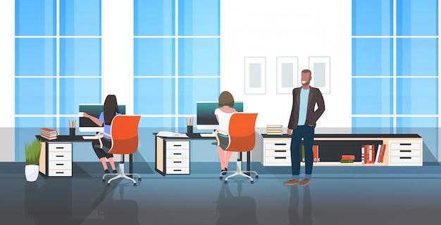 Männlicher chef, der durch das büro geht und weibliche arbeiter kontrolliert