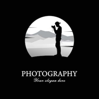 Männlicher fotograf der schattenbild, der die kamera betrachtet