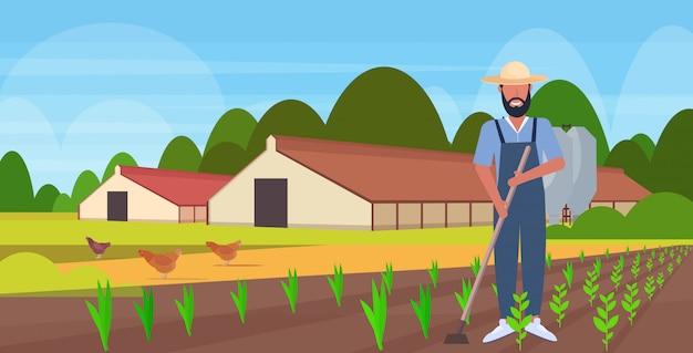 Männlicher gärtner unter verwendung von hacke landsmann hackplatz mit saatpflanzen feldpflanzung ernte gartenarbeit öko-landwirtschaftskonzept ackerland landschaft landschaft in voller länge horizontal