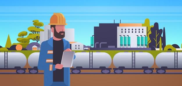 Männlicher ingenieur im helm unter verwendung der tablette, die zugtanks mit öl- und kraftstofffabrik steuert