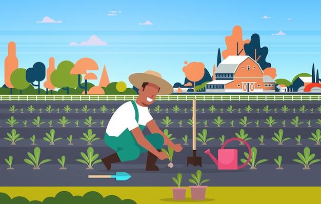 Männlicher landwirt, der junge sämlinge pflanzt, pflanzt gemüsemann, der im gartenlandwirt arbeitet öko-landwirtschaftskonzept ackerland feldlandschaftslandschaft in voller länge horizontal