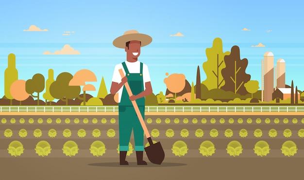 Männlicher landwirt, der schaufel hält, die grünkohl pflanzt gemüse ackerland feld landschaft landschaft öko landwirtschaft konzept horizontale volle länge flach