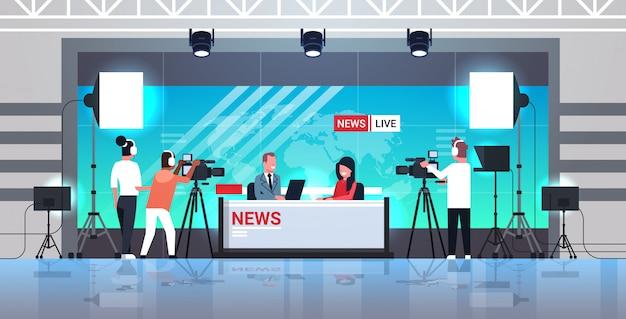 Männlicher moderator interviewt frau im fernsehstudio tv live-nachrichtensendung videokamera shooting crew broadcasting konzept flach in voller länge horizontal