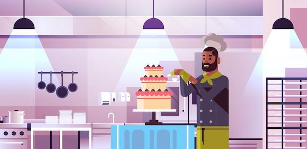 Männlicher professioneller kochgebäckkoch, der leckeren hochzeitscremekuchen-afroamerikanermann im einheitlichen kochenden nahrungsmittelkonzept des modernen restaurantkücheninnenporträts verziert