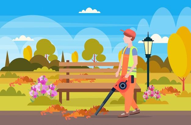 Männlicher straßenreiniger hält blätter gebläsemann im einheitlichen reinigungsdienstkonzept stadtstadtparklandschaftshintergrund in voller länge flach horizontal