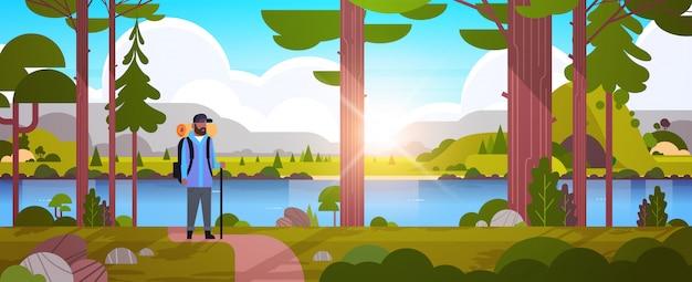 Männlicher touristenwanderer mit dem rucksackmannreisenden, der stock hält, der im waldwanderkonzept sonnenaufganglandschaft naturflussgebirgshintergrund horizontale volle länge steht
