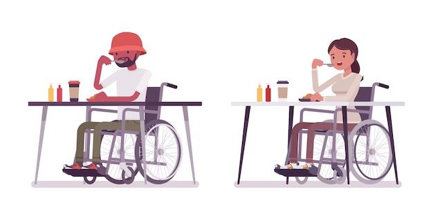Männlicher und weiblicher junger rollstuhlbenutzer, der essen isst, das am tisch sitzt