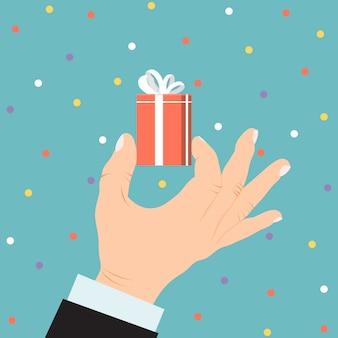 Männliches geschäft hand halten geschenk box geschenk, weihnachts souvenir lokalisiert auf blaue illustration. konzept urlaub konfetti.