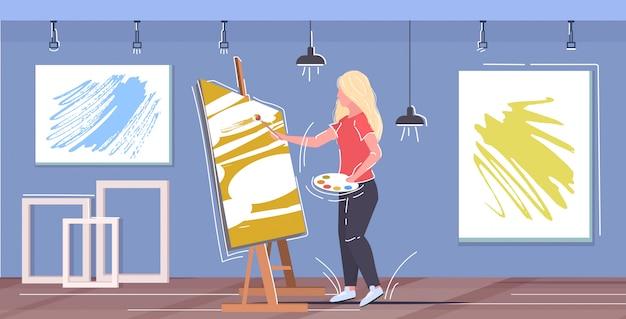 Maler, der pinsel und palettenkünstlerin verwendet, die vor dem modernen werkstattstudio-innenraum des staffelei-kunstkonzepts horizontal stehen