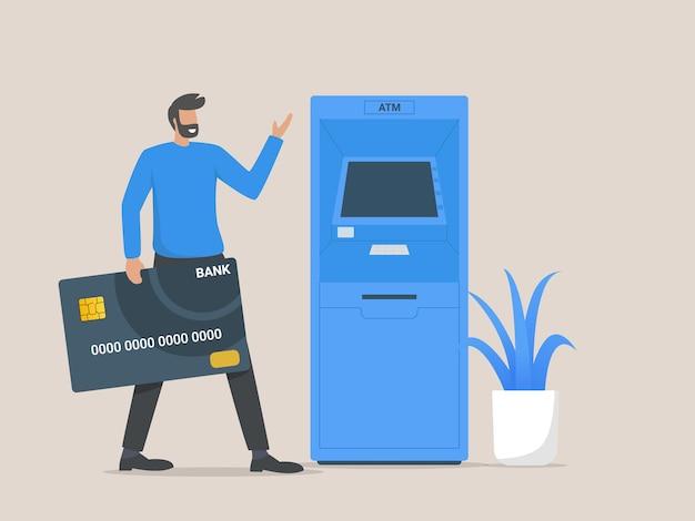 Man kunde steht in der nähe von geldautomaten und hält kreditkarte