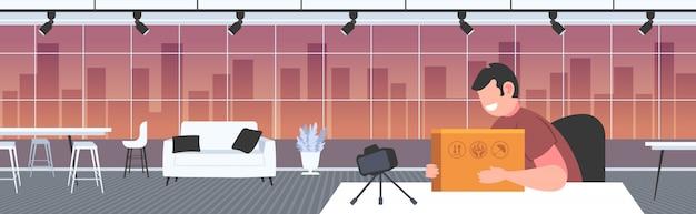 Mann blogger öffnen paket box aufzeichnung unboxing video mit kamera auf stativ blogging mail zustellungskonzept büro innen horizontales porträt