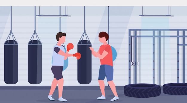 Mann boxer mit personal trainer schlagen boxsack in roten boxhandschuhen kerl kämpfer training training modernen kampf club gym interieur gesunden lebensstil konzept flach horizontal