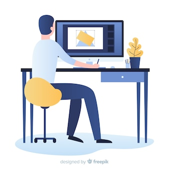 Mann, der am grafikdesignerarbeitsplatz sitzt