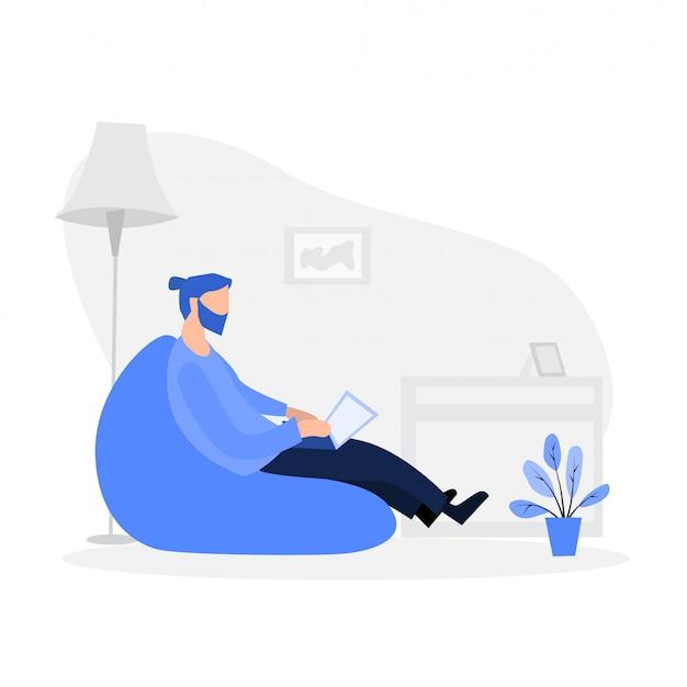Mann, der auf dem puffsessel sitzt und zu hause am laptop arbeitet