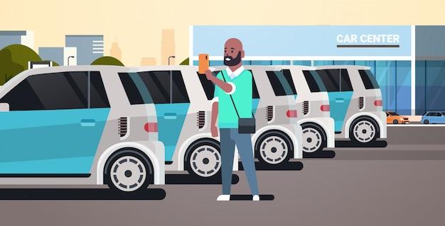 Mann, der das fahrzeug auf dem parkplatz des autozentrums wählt, unter verwendung des carsharing-konzepttyps der mobilen anwendung kerl, der smartphone-online-autovermietungsdienst horizontal hält