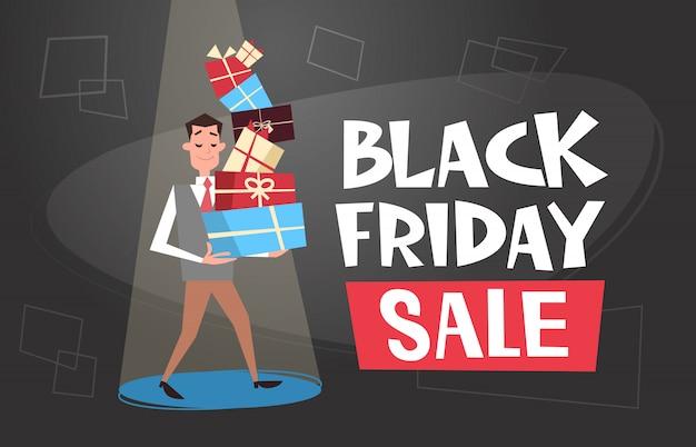 Mann, der geschenkbox-stapel, black friday-verkaufs-einkaufsfahne hält