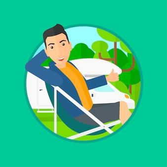 Mann, der im stuhl vor reisemobil sitzt.