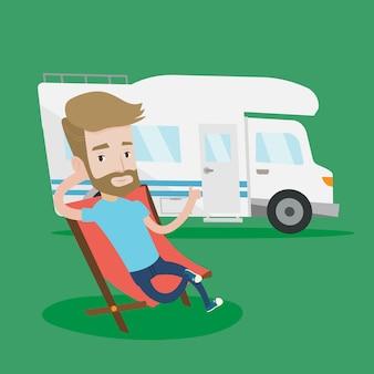 Mann, der im stuhl vor wohnmobil sitzt.