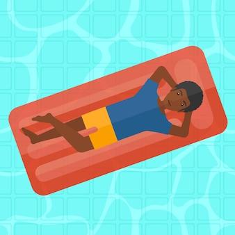 Mann, der im swimmingpool sich entspannt.