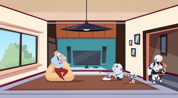 Mann, der im wohnzimmer sich entspannt, während gruppe roboter-haushälterinnen haus säubern
