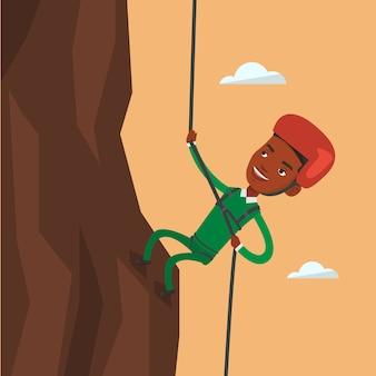 Mann, der in den bergen mit seil klettert.