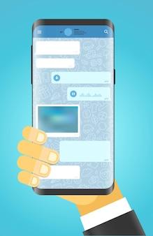 Mann, der modernes smartphone hält moderne smartphone-messenger-app