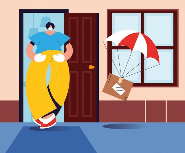Mann, der paketbox fängt, der mit fallschirm vom himmel fällt