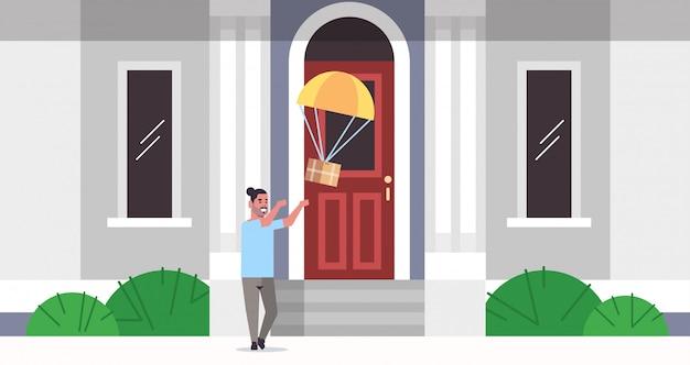 Mann, der paketbox fängt, der mit fallschirm vom himmeltransport-versandpaket herunterfällt luftpost express-postzustellungskonzept modernes hausgebäude außen in voller länge flach horizontal