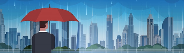 Mann, der regenschirm-blick auf sturm im stadt-enormen regen-hintergrund-hurrikan-tornado im stadtnaturkatastrophen-konzept hält