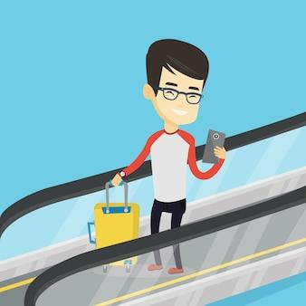 Mann, der smartphone auf rolltreppe im flughafen verwendet.