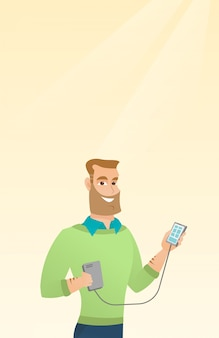 Mann, der smartphone von der tragbaren batterie wieder auflädt